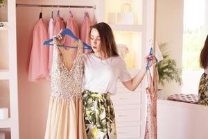 hübsche Frau, die Kleidung oder Outfit in der Umkleidekabine auswählt foto