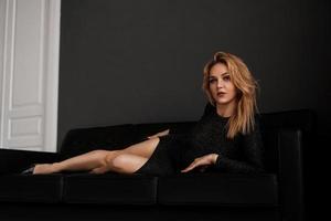schönes Mädchen im schwarzen Kleid liegt auf der Couch foto