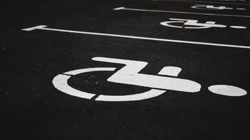 Parkplatzschild für Behinderte auf dunklem Backstein foto