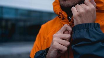 ein Mann befestigt seine Arbeitsuniform. orangefarbene Arbeiteruniform - Nahaufnahme foto