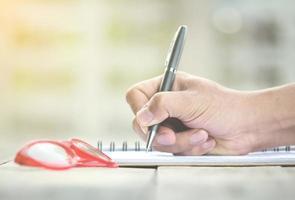 Person, die Notizen mit Brille auf dem Schreibtisch schreibt foto
