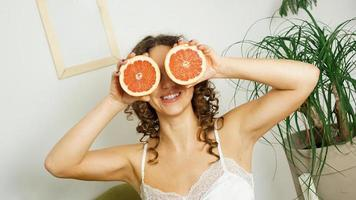 Porträt einer Frau, die ihr Auge mit Grapefruit bedeckt foto