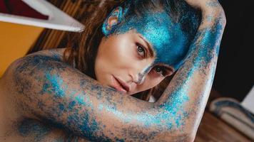 Frau mit Funkeln im Gesicht. Mädchen mit Kunst Make-up foto