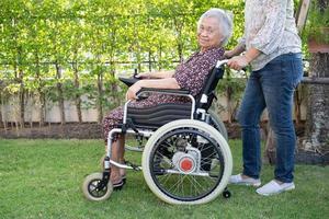 Arzt hilft asiatischer Seniorin, die im Rollstuhl im Park sitzt foto
