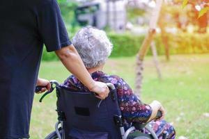 helfen und unterstützen Sie asiatische ältere Patientin, die im Rollstuhl sitzt foto