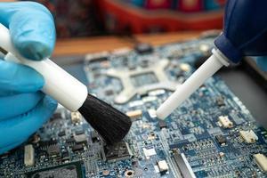 Techniker verwenden Bürste, um Staub im Leiterplattencomputer zu reinigen. foto