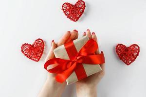 Geschenk mit einem roten Band in den Händen auf einem weißen Hintergrund foto