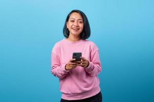 fröhliche junge asiatische frau, die smartphone hält und glücklich nach vorn schaut foto
