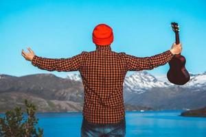 Kerl mit Gitarre vor dem Hintergrund von Bergen, Wäldern und See foto