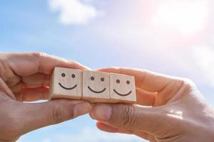 Lächeln Sie Gesicht und Warenkorb-Symbol auf Holzwürfel. optimistische Person. foto