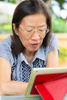 Reife Frau mit digitalem Tablet zu Hause foto