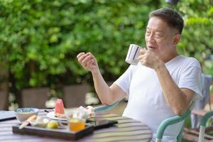 reifer Mann, der gesundes Frühstück im Garten isst foto