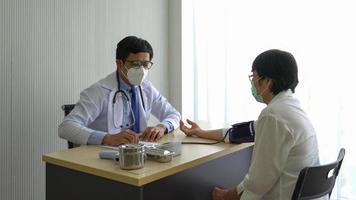 Arzt misst Blutdruck foto