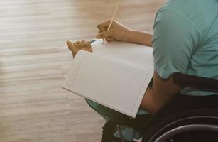 Frau arbeitet und sitzt im Rollstuhl foto
