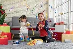 Mutter und Kind feiern Weihnachten mit Konfetti zu Hause foto