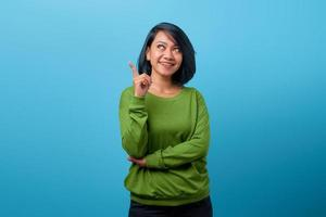 attraktive asiatische frau mit lächeln und mit dem finger nach oben zeigend foto
