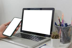 Verspotten Sie die Hand, die einen weißen Laptop mit leerem Bildschirm des Smartphones auf dem Schreibtisch hält foto