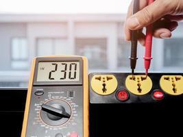 Messen Sie die Wechselspannung von 230 Volt mit einem digitalen Messgerät. foto