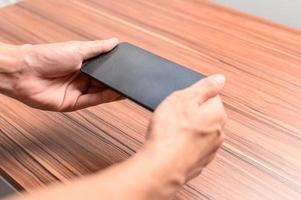 Hand mit Smartphone am Schreibtisch foto