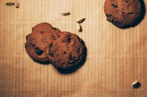 Draufsicht auf knusprige Schokoladenkekse mit Kardamom auf strukturiertem Pergamenthintergrund. Platz für Ihren Text und Design foto