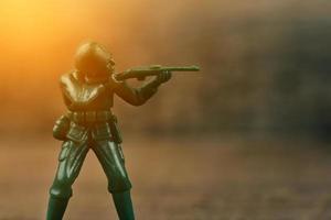 Soldat, der eine auf den Feind gerichtete Waffe hält foto