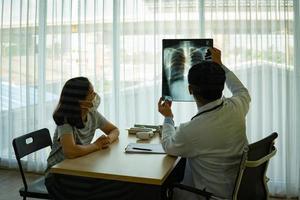 Arzt zeigt Patienten mit Masken ein Röntgenbild foto