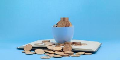 Münzen in einer Tasse und einem Buch foto