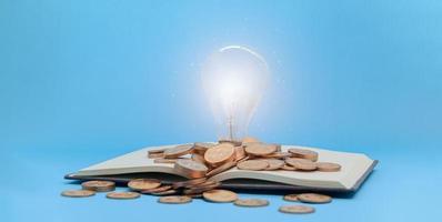Glühbirne und Münzen auf einem Buch foto