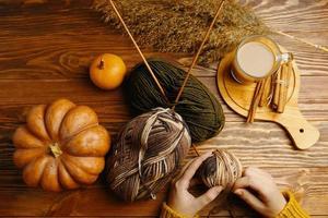 Hände im orangefarbenen Pullover mit Garn, Stricknadeln, Kaffee und Zimtstangen auf Holztisch foto