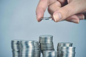 Frauenhand legt silberne Geldmünzen zum Stapeln foto