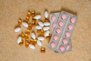 Blister mit rosa Tabletten und Vitamin D und Kapseln mit Fischöl foto