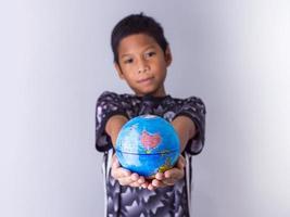 Junge, der einen Globus hält, steht vor der Tür. foto