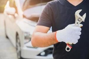 Automechaniker, der Schraubenschlüssel in der Nähe von Auto hält. Auto-Wartungskonzept. foto
