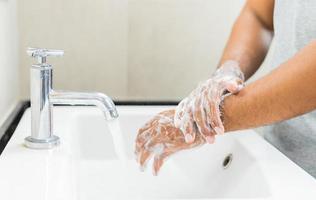 Mann wäscht sich die Hände mit Seife. foto