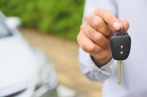 Geschäftsmann, der einen Autoschlüssel gibt. immer neues Autokonzept. foto