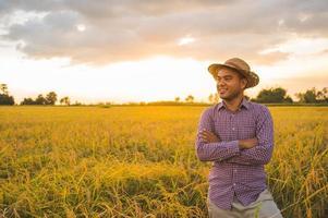 junger asiatischer Bauer und Reisfeld foto