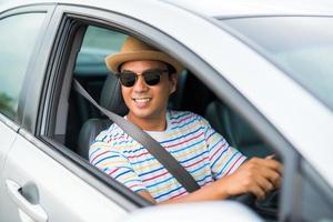 junger gutaussehender asiatischer mann, der auto fährt, um zu reisen. foto