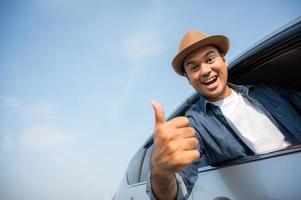 junger gutaussehender asiatischer mann, der auto fährt, um zu reisen foto
