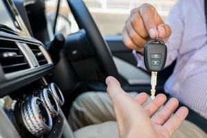 Geschäftsmann, der einen Autoschlüssel beim Sitzen im Auto gibt. foto