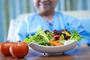 asiatischer älterer Fraupatient, der im Krankenhaus frühstückt. foto