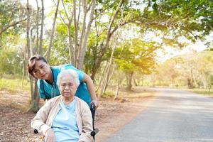 Hilfe und Pflege asiatische Seniorin, die auf Rollstuhl im Park sitzt. foto