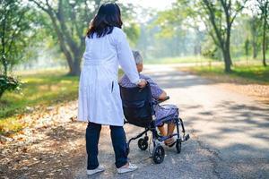 Arzt Hilfe und Pflege asiatische Seniorin verwendet Walker im Park. foto