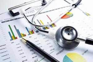 Stethoskop auf Millimeterpapier. Geschäftsdaten des Finanzkontos. foto