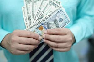 Geschäftsmann, der uns Dollar-Banknoten Geld hält foto