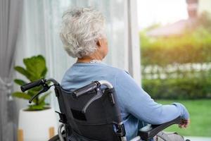 ältere Frau sitzt im Rollstuhl und schaut aus dem Fenster foto