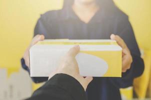 eine menschliche hand, die paket und briefkasten für lieferung und versand hält. foto