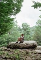 Frau sitzt auf einem großen Felsen im Wald, ruht sich aus oder meditiert foto