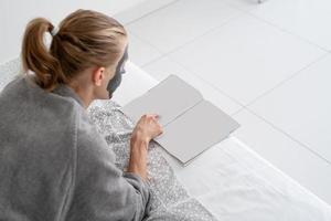 Frau mit Gesichtsmaske, die entspannt auf dem Bett liegt und eine Zeitschrift liest foto
