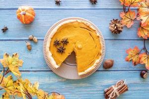 hausgemachter Kürbiskuchen mit Herbstlaub auf rustikalem Hintergrund, Ansicht von oben foto