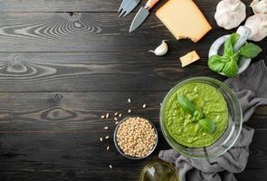 frisches Pesto in Schüssel mit Zutaten, Draufsicht flach auf Schwarz legen foto